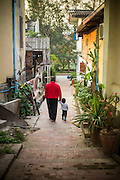 12 MARCH 2013 - LUANG PRABANG, LAOS: A man and his son walk down a small street in Luang Prabang, Laos. Luang Prabang has more than 30 temples and is a UNESCO World Heritage Site. It is the most visited tourist attraction in Laos.  PHOTO BY JACK KURTZ