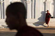 Out of focus Monk walks past as another leans on white wall and looks on, Shwe Yan Pyay Monastery, Nyaung Shwe