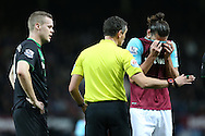 Referee Andre Marriner asks Andy Carroll of West Ham United to leave the pitch for treatment after being fouled by Ryan Shawcross, the Stoke City captain. Barclays Premier league match, West Ham Utd v Stoke city at the Boleyn Ground, Upton Park  in London on Saturday 12th December 2015.<br /> pic by John Patrick Fletcher, Andrew Orchard sports photography.