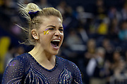 Annie Maxim of the Michigan Wolverines celebrates after her completing her vault routine at the Flip for Chip meet against Nebraska at the Crisler Center on February 3, 2018 in Ann Arbor, Michigan.