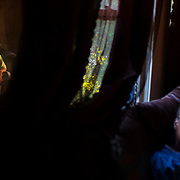 """Ellen Wilson (reflected) and her daughter Adrian """"Nikki"""" Wilson sit in their living room in the Baptist Town neighborhood of Greenwood, Mississippi on October 17, 2013. Ellen suffers from a myriad of health issues and Nikki works at the nearby Heartland Catfish plant, gutting fish, in order to help support herself and her family."""