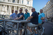 Summertime in London, England, UK. The Pedibus is an 8 seater cycle with bar. Group of friends enjoying a Pedal Bus tour. The Pedibus London Tours are a fun way for groups of people to enjoy the sights, while celebrating and having a drink. Often for birthdays, stag or hen parties etc.
