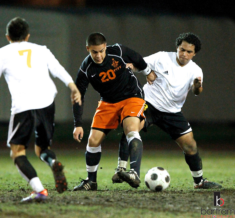 Antioch High's Rene Gonsalez, right, and Pittsburg High's Javier Valencia battle for the ball while Antioch's Jordan Cisneros watches during their game at Antioch High School on Tuesday, Feb. 7, 2012. (Photo by Kevin Bartram)