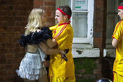© Licensed to London News Pictures . 27/12/2017. Wigan, UK. An argument between a man and a woman in which a woman hits the man with a costume prop and then the man grabs the woman around the neck. Revellers in Wigan enjoy Boxing Day drinks and clubbing in Wigan Wallgate . In recent years a tradition has been established in which people go out wearing fancy-dress costumes on Boxing Day night . Photo credit: Joel Goodman/LNP
