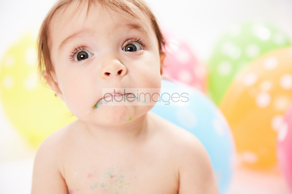 Close up of Baby Girl with Food on Mouth