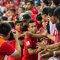 Ismadi Mukhtar (#13) of Singapore shares a moment with Singapore fans after the 1-3 loss against Malaysia during the group stage match of the AFF Suzuki Cup at the National Stadium at the Singapore Sports Hub on November 29, 2014, in Singapore.