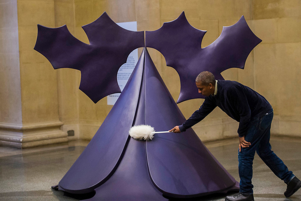 Phillip King's Genghis Khan is dusted by art handler Mikei Hall. <br /> Phillip King exhibition at the Tate Britain, to mark his 80th birthday. The display celebrates King's significant contribution to late 20th century sculpture through six colourful sculptures. These are his key works from the 1960s and include a variety of unusual shapes and forms, demonstrate King's experimentation with abstraction, construction, material and colour. They include iconic sculptures such as Genghis Khan 1963, a conical structure with a pair of antler-like forms and Rosebud 1962, his first coloured sculpture using fibreglass. The works are displayed in the grand surroundings of the Duveen galleries at Tate Britain.