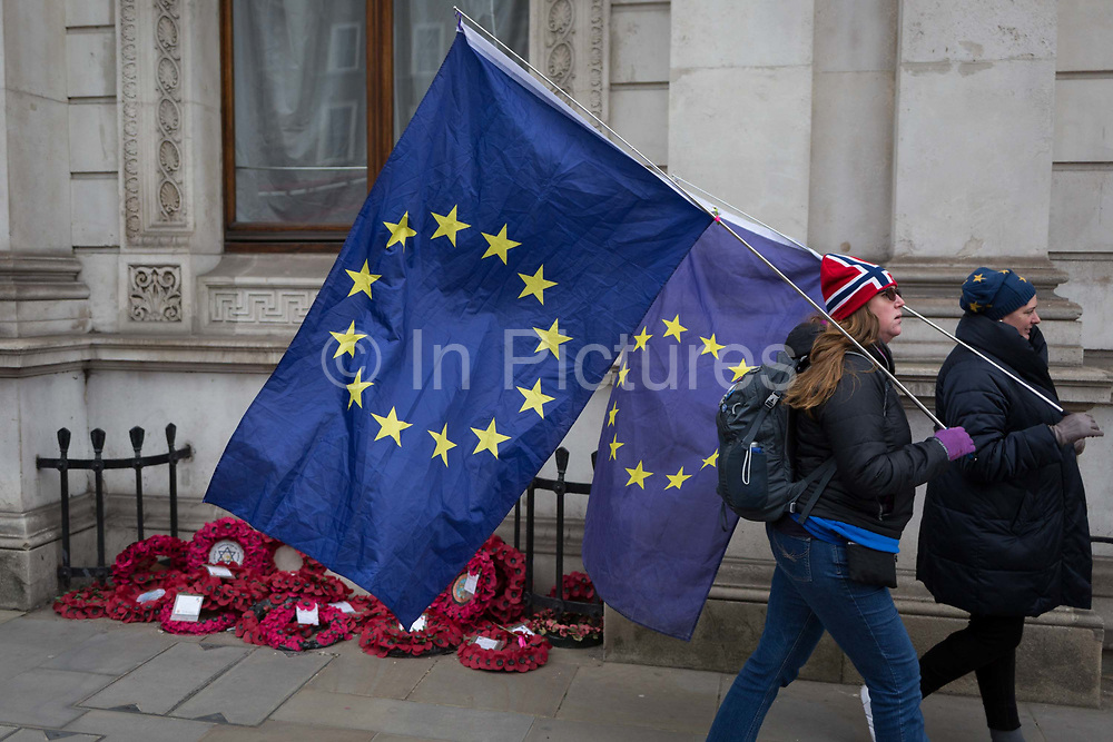As the EUs Chief negotiator Michel Barnier meets Theresa May in London to discuss the next stage of Brexit, anti-Brexit protesters walk past war memorial wreaths while holding the stars of the EU flag in Whitehall and near Downing Street, the official residence of the Prime Minister, on 5th February 2018, in London England.