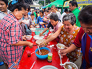 """07 AUGUST 2014 - BANGKOK, THAILAND:   People put chilies and condiments on their noodle soup during a community food distribution program at Pek Leng Keng Mangkorn Khiew Shrine in Bangkok. Thousands of people lined up for food distribution at the Pek Leng Keng Mangkorn Khiew Shrine in the Khlong Toei section of Bangkok Thursday. Khlong Toei is one of the poorest sections of Bangkok. The seventh month of the Chinese Lunar calendar is called """"Ghost Month"""" during which ghosts and spirits, including those of the deceased ancestors, come out from the lower realm. It is common for Chinese people to make merit during the month by burning """"hell money"""" and presenting food to the ghosts. At Chinese temples in Thailand, it is also customary to give food to the poorer people in the community.      PHOTO BY JACK KURTZ"""