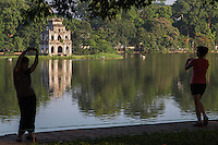 """Hoan Kiem Lake or """"Lake of the Returned Sword"""" is a lake in old city of Hanoi. The lake serves as a focal point for Hanoi public life.  It is a popular spot for jogging, exercising and early morning tai chi sessions along its banks. In the background is Turtle Tower, which is also called Tortoise Tower, a small tower in the middle of Hanoi's Hoan Kiem Lake."""