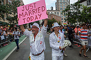"Giovanni Miranda and Todd Fernandez  march with a sign that reads ""Just Married Today."" They were, in fact, just married the day of the parade."