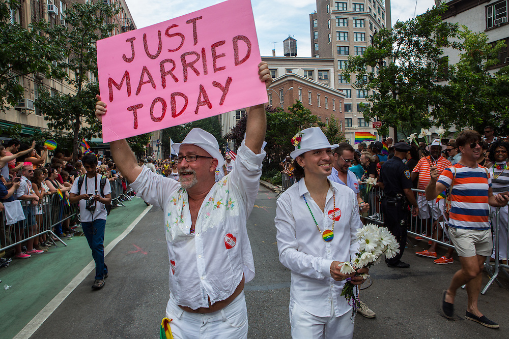 """Giovanni Miranda and Todd Fernandez  march with a sign that reads """"Just Married Today."""" They were, in fact, just married the day of the parade."""
