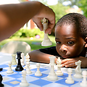 """Isaiah Nelson, 7, back, watches as Laquan Smith, 11, makes a play while they play chess during the """"Chillin' and Grillin' with the Chief"""" community event at Ottawa Park in Toledo on Monday, July 8, 2019. THE BLADE/KURT STEISS <br /> CTY IceCream09"""