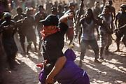Un hombre voluntario golpea a los judíos con una soga mientras protege a un niño que representa al niño Jesús durante la representación de las 12 estaciones en Huaynamota, Nayarit.
