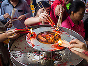 """19 FEBRUARY 2015 - BANGKOK, THAILAND:  People light candles and incense on Chinese New Year at Wat Mangkon Kamalawat in Bangkok. 2015 is the Year of Goat in the Chinese zodiac. The Goat is the eighth sign in Chinese astrology and """"8"""" is considered to be a lucky number. It symbolizes wisdom, fortune and prosperity. Ethnic Chinese make up nearly 15% of the Thai population. Chinese New Year (also called Tet or Lunar New Year) is widely celebrated in Thailand, especially in urban areas that have large Chinese populations.   PHOTO BY JACK KURTZ"""