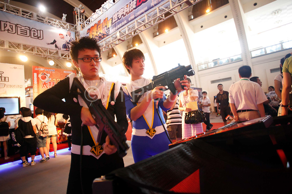 Youngsters dressed in cartoon costumes play a shooter video game at an Anime and Cosplay festival and enjoying a rare opportunity of carefree fun in Shanghai, China on 03 July 2009.  Chinese youth face one of the toughest school system and most unrealistic parental expectation level in the world, a recent survey showed that three-quarters of parents expect their children to achieve scores above 90%, and almost one in ten expects their children to achieve perfect scores in all subjects.