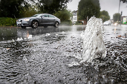 © Licensed to London News Pictures. 23/09/2018. Leatherhead, UK.  Rain water gushes through a manhole cover in Leatherhead, Surrey - as heavy rain hits parts of the south. Warmer temperatures are expected in a few days.  Photo credit: Peter Macdiarmid/LNP