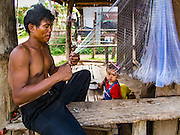 18 JUNE 2016 - DON KHONE, CHAMPASAK, LAOS:  A fisherman repairs his nets on Don Khon Island in the 4,000 Islands area of southern Laos. Most of the families on Don Khon make their living either by fishing or farming, or sometimes, both. Fishermen in the area are contending with lower yields and smaller fish, threatening their way of life. The Mekong River is one of the most biodiverse and productive rivers on Earth. It is a global hotspot for freshwater fishes: over 1,000 species have been recorded there, second only to the Amazon. The Mekong River is also the most productive inland fishery in the world. The total harvest of fish from the Mekong is approximately 2.5 million metric tons per year. By some estimates the harvest in the Tonle Sap (in Cambodia) had doubled from 1940 to 1995, but the number of people fishing the in the lake has quadrupled, so the harvest per person is cut in half. There is evidence of over fishing in the Mekong - populations of large fish have shrunk and fishermen are bringing in smaller and smaller fish.        PHOTO BY JACK KURTZ