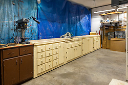 A woodworkers workshop occupying space in a large garage sports a drill press, power mitre box saw, several handmade cabinets with counter space, a custom made storage box, a clamp rack and several organizers