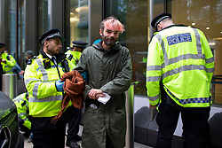 © Licensed to London News Pictures. 14/10/2019. London, UK. An Extinction Rebellion protester is removed from the  doors of the Barclays offices in Canary Wharf . Today protesters will target the financial district. Photo credit: George Cracknell Wright/LNP