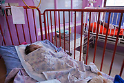 A baby named Samkelo sleeps in a hospital cot bed. Samkelo is dying from liver disease and is a pediatric palliative patient in Baragwanath Hospital in Johannesburg, South Africa.  Baragwanath is the third biggest hospital in the world, and the first hospital that Bigshoes Foundation has provided palliative care to, a service that was previously non existent in South Africa.