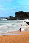 Lone surfer on beach, Oahu, Hawaii RIGHTS MANAGED LICENSE AVAILABLE FROM www.gettyimages.com -- contact Sheldon for details