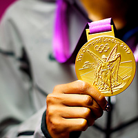 After a press conference, American sprinter Sanya Richards-Ross poses with her 400 meter gold medal during the 2012 London Summer Olympics.