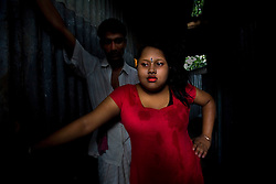 Sex worker Munnie, 15, looks for a customer at a brothel in Tangail, Bangladesh.