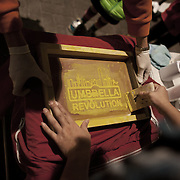 """As part of the remaining Umbrella Movement tent camp a couple of people offer free screen prints with art work related to the political movement to any passers-by. The pop-up screen printing is set up on a small table outside the public toilets under a fly-over. The Umbrella Movement and tent camps were cleared off the streets shortly before Christmas by police but a small number of tents have been allowed to remain outside the Govenment offices. <br /> <br /> Hong Kong (香港; """"Fragrant Harbour""""), officially known as Hong Kong Special Administrative Region of the People's Republic of China since the hand-over from the United Kingdom in 1997 under the principle of """"one country, two systsems"""".  7 million people live on 1,104km square, making it the most vertivcal city in the world. Hong Kong is one of the world's leading financial centres along side London and New York, it has one of the highest income per capita in the world as well the moste severe income inequality amongst advanced economies. The Hong Kong civil society is highly regulated but has at the same time one of the most lassiez-faire economies with low taxation and free trade. Civil unrest and political dissent is unusual but in 2014 the Umbrella Movenment took to the streets of Hong Kong demanding democracy and universal suffrage. 93 % are ethnic Chinese, mostly Cantonese speaking."""