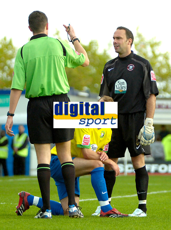Photo: Ed Godden.<br /> Milton Keynes Dons v Hereford United. Coca Cola Championship. 21/10/2006. Referee Darren Deadman tells Hereford's Trent McClenahan to get up and is watched on by his keeper Wayne Brown (R).