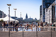 fountain at the Harry-Blum square in the Rheinau harbor, view to the catehdral, Cologne, Germany.<br /> <br /> Springbrunnen am Harry-Blum-Platz im Rheinauhafen, Blick zum Dom, Koeln, Deutschland.