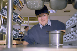 Portrait of woman with learning disability working in canteen,