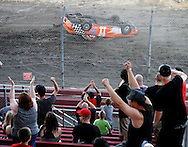 Spectators cheer as Chris Lionel flips his car during the rollover contest at the Antioch Speedway during the Contra Costa County Fair in Antioch on Sunday, June 3, 2012.  Lionel won the event and was the only competitor who managed to roll his car. (Photo by Kevin Bartram)