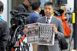 © Licensed to London News Pictures. 04/06/2017. London, UK. A TV news crew shows the morning headlines.  Police cordons continue to be in place around London Bridge after the previous night's terrorist attack where a reported three attackers were shot by the police and seven members of the public died after being attacked with knives.  Photo credit : Stephen Chung/LNP