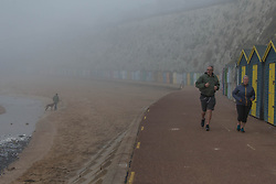 © Licensed to London News Pictures.  20/04/2021. Broadstairs, UK. Members of the public jog through the foggy dawn at Viking Bay in Broadstairs, east of Kent. As a mini heatwave is forecast to hit parts of UK this week with high temperatures reaching 22 celsius. Photo credit: Marcin Nowak/LNP