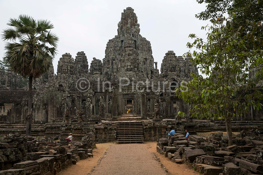 A landscape view of Bayon Temple which stands in the centre of the walled temple complex of Angkor Thom, Siem Reap Province, Cambodia, South East Asia.  The temple was built around 1190 AD by King Jayavarman VII as a Buddhist temple, but it incorporates elements of Hindu cosmology.  In the centre is a statue of Buddha with a yellow tunic.