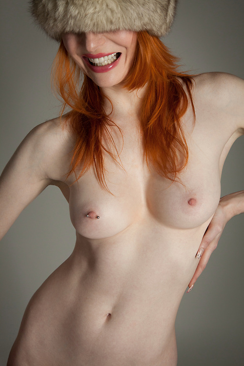 Portrait of nude woman with red hair wearing a fur hat against a gray backdrop