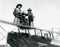 1921 Two wing walkers sit at table on the wing of a Hisso Jenny airplane at Rogers Field at Wilshire Blvd. & Fairfax Ave.
