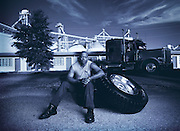 An african-american sits down with a big tire from his 18 wheeler truck.