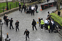 RETRANSMISSION ADDING DETAIL THAT POLICEMAN IS POINTING A GUN AT THE MAN ON THE FLOOR ON THE TOP OF THE FRAME A policeman points a gun at a man on the floor at the top of the frame as emergency services attend the scene outside the Palace of Westminster, London, after policeman has been stabbed and his apparent attacker shot by officers in a major security incident at the Houses of Parliament.