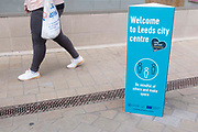 A woman carrying a bag of shopping walks past a sign advising people to be mindful and keep a distance from others to prevent the spread of Covid-19 on 11th August, 2021 in Leeds, United Kingdom. The British Department of Health has announced that as of Monday, new guidance will mean that even the fully vaccinated will be advised to wear a mask and limit their contact with others if they come into contact with somebody who tests positive for Coronavirus.