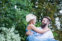 Happy young man carrying woman in garden, Bavaria, Germany