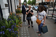 Shoppers near Sloane Square check their mobiles phones on 24th May 2017 in London, United Kingdom.  From the series Our Small World, an observation of our mobile phone obsessions