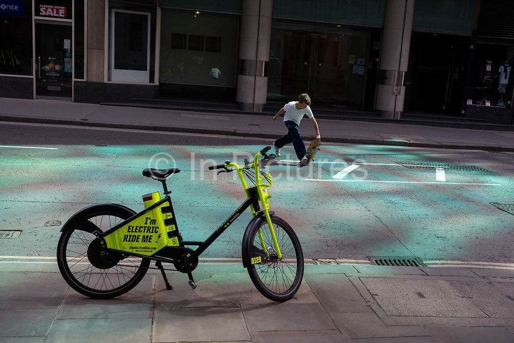 A young skateboarder makes a dash across Fenchurch Street where an electric rental Freebike stands on the pavement in reflected light, in the City of London, the capitals financial district, on 20th July 2020, in London, England.