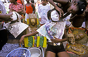 A group of children make papier mache masks under the direction of a social NGO programme known as Bagunarte, on the streets of Alagados an impoverished district of Salvador de Bahia, Brazil.