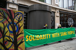 London, UK. 24th July, 2021. Activists from the Forest Rebellion, known as Skogsupproret in Sweden, protest with a banner and artwork outside the premises of the Timber Trade Federation at the Building Centre. The activists were protesting against the clearcutting of natural forests in Sweden and the social and environmental impacts of timber imports from Swedish logging companies with UK subsidiaries belonging to the Timber Trade Federation, whilst also standing in solidarity with the indigenous Sami people of northern Scandinavia and demanding that their rights be respected. Sweden is the largest lumber supplier to the UK.