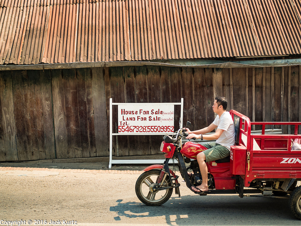 """13 MARCH 2016 - LUANG PRABANG, LAOS: A Lao man rides his tractor past a home for sale in Luang Prabang. The for sale sign being in English indicates who the property is being marketed to. Luang Prabang was named a UNESCO World Heritage Site in 1995. The move saved the city's colonial architecture but the explosion of mass tourism has taken a toll on the city's soul. According to one recent study, a small plot of land that sold for $8,000 three years ago now goes for $120,000. Many longtime residents are selling their homes and moving to small developments around the city. The old homes are then converted to guesthouses, restaurants and spas. The city is famous for the morning """"tak bat,"""" or monks' morning alms rounds. Every morning hundreds of Buddhist monks come out before dawn and walk in a silent procession through the city accepting alms from residents. Now, most of the people presenting alms to the monks are tourists, since so many Lao people have moved outside of the city center. About 50,000 people are thought to live in the Luang Prabang area, the city received more than 530,000 tourists in 2014.    PHOTO BY JACK KURTZ"""