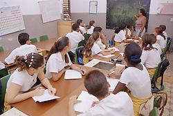 Secondary school children sitting at desks in classroom with teacher,