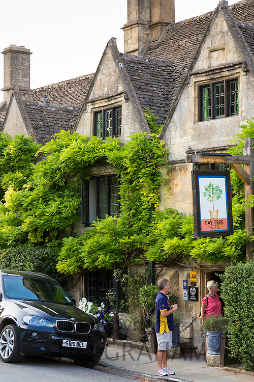 Couple at the Bay Tree Hotel a traditional old gastro pub hotel with Range Rover parked, Burford, The Cotswolds, Oxfordshire, UK