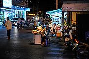 Woman selling bread beneath a bare light globe. Vung Tau, Vietnam